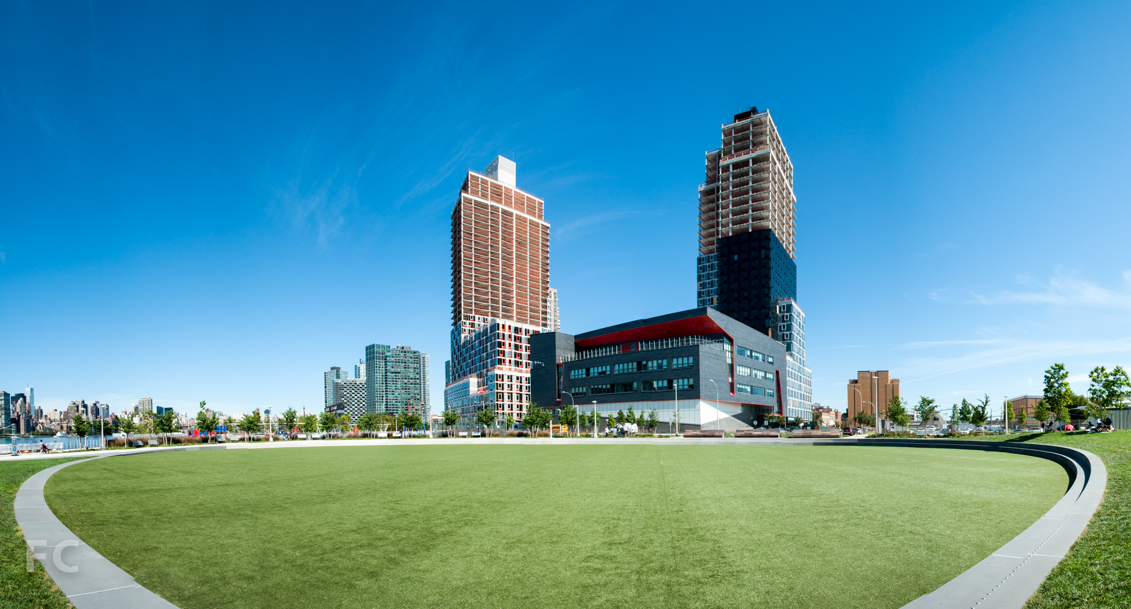 Building A (left) and Building B (right) from the oval green at Hunters Point South Park.