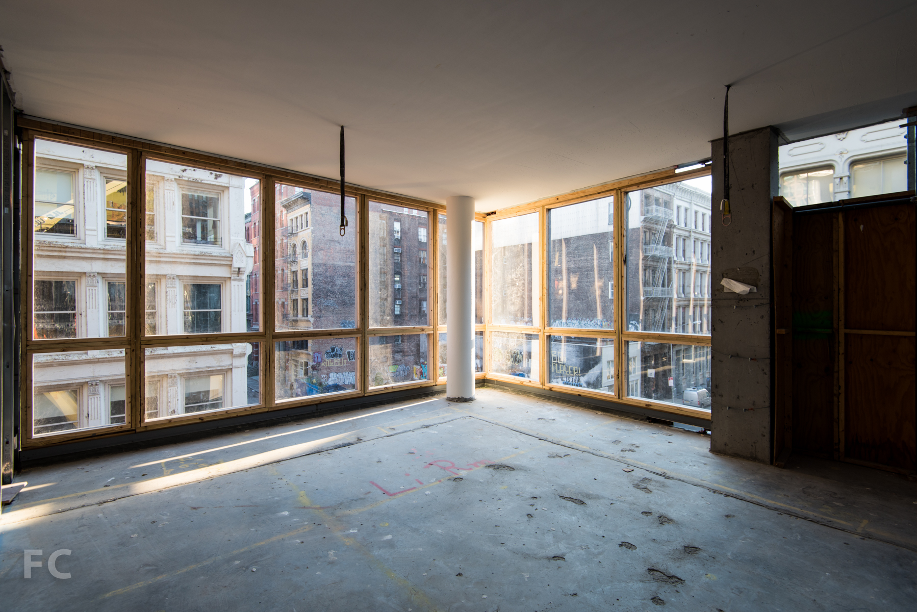 The corner living room of the B unit, looking out onto the intersection of Grand Street and Wooster Street.