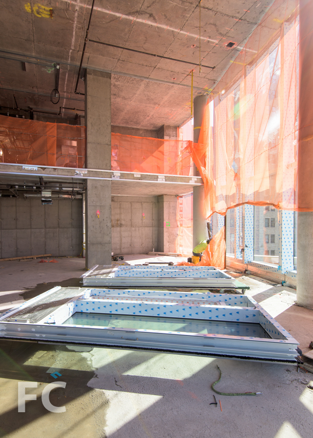 Curtain wall panels await installation in a double height living room.