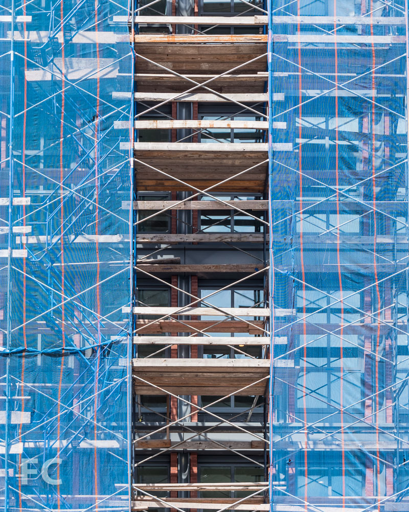 Detail of the façade of 372 Lafayette Street from behind construction scaffolding.