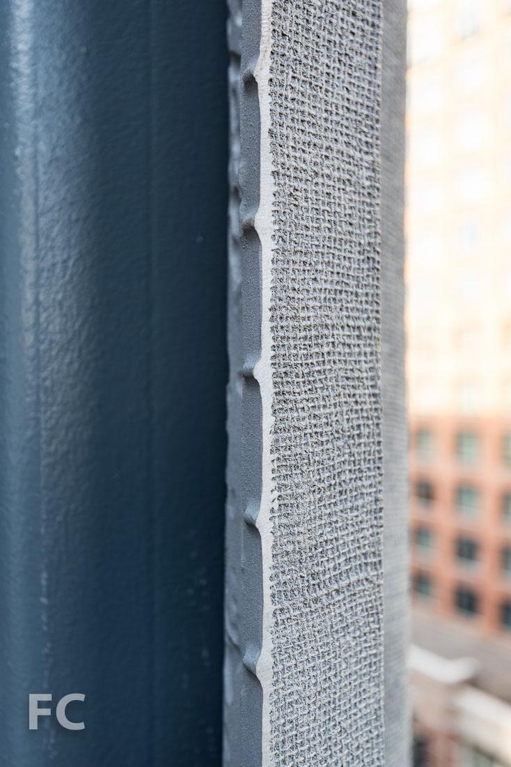 Burlap imprint on the street face of the facade screen.