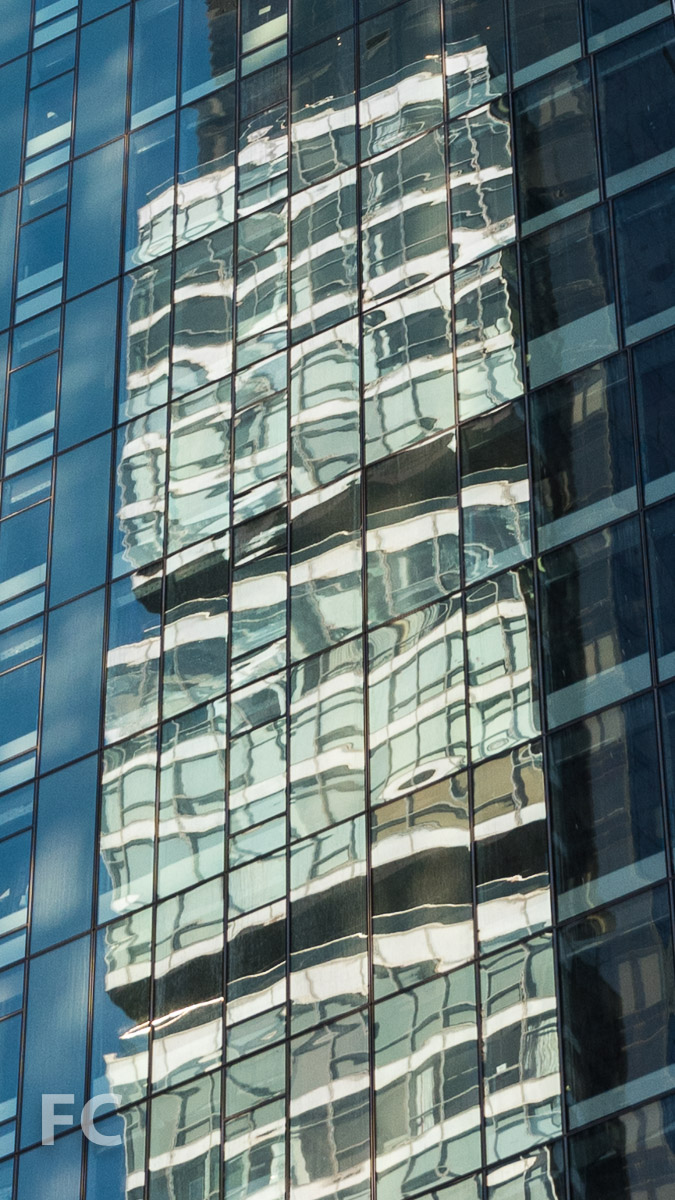 One Madison reflected in the glass curtain wall.