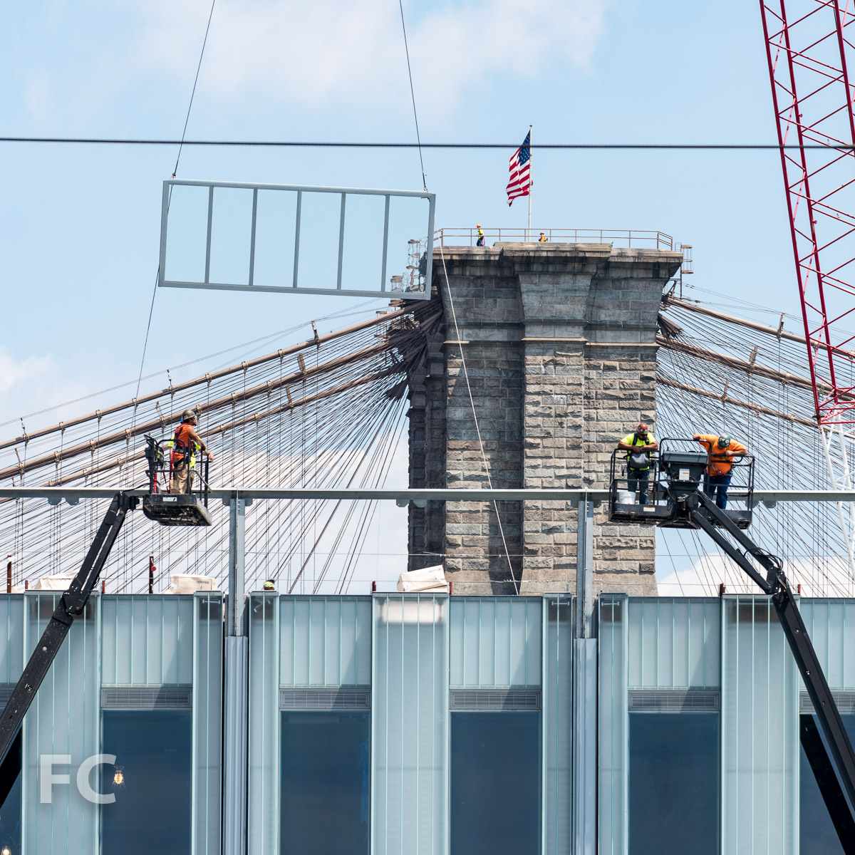 A glass wall panel being hoisted into place.