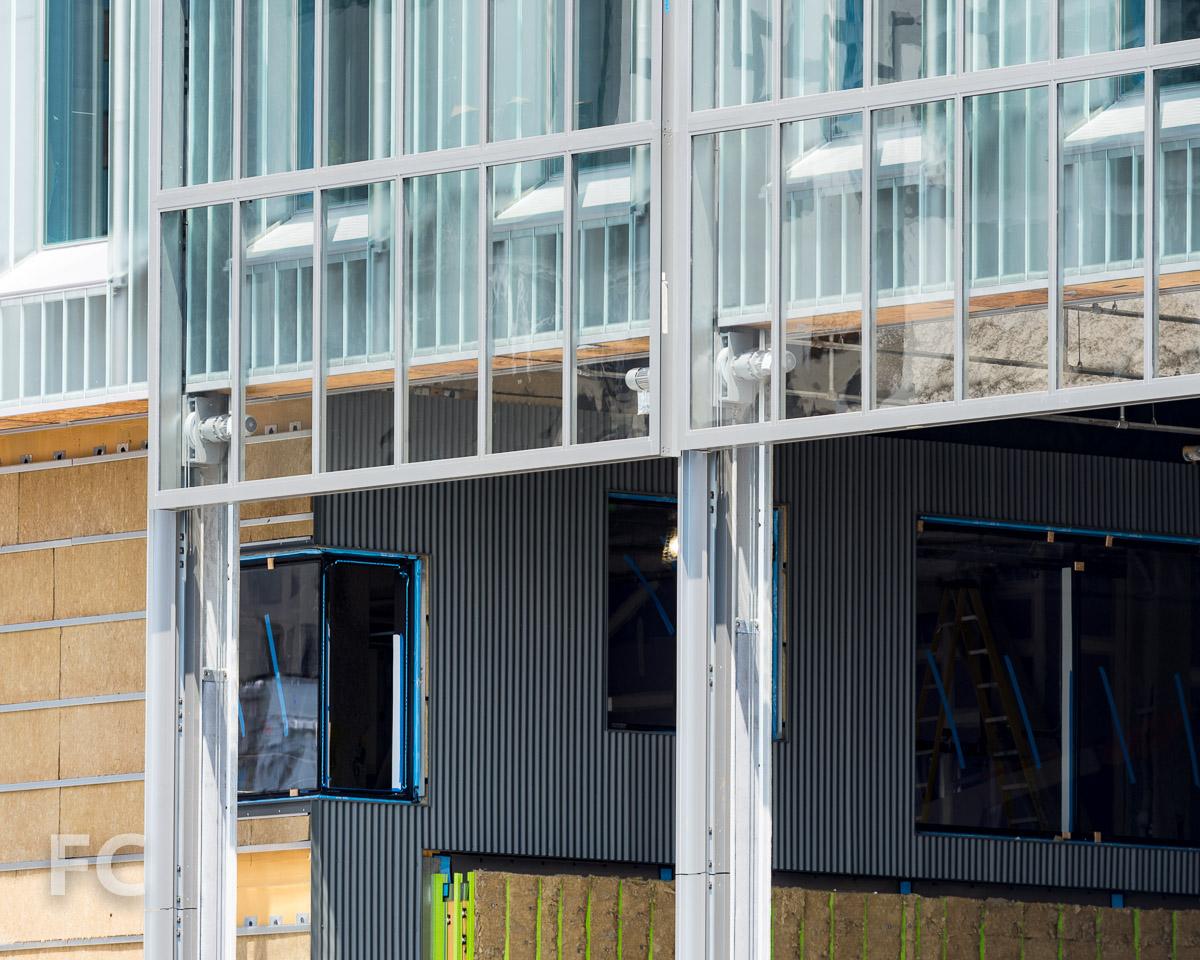 Corrugated metal panel façade installed on the lower floors.