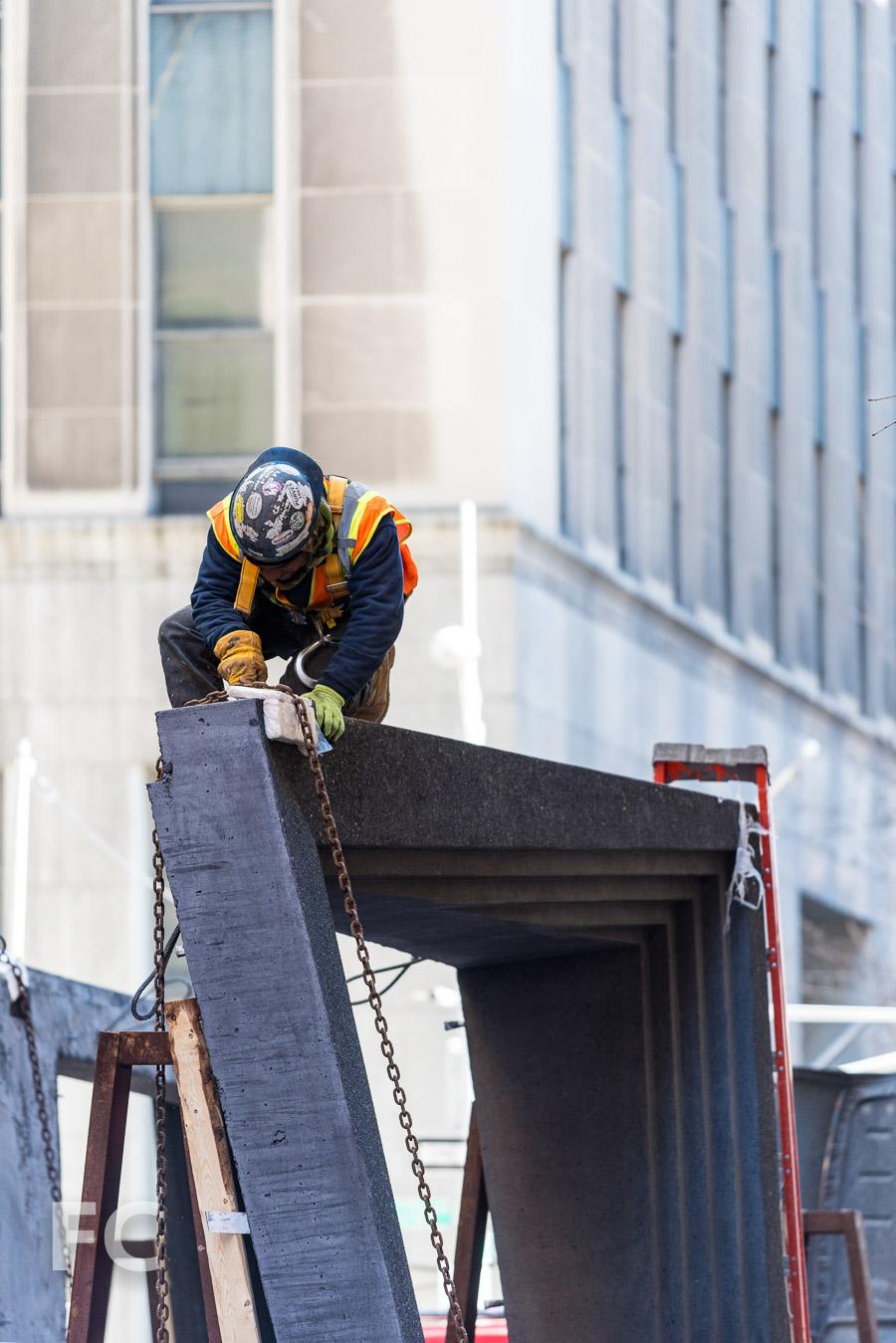 Construction worker prepares precast panel for the crane lift.