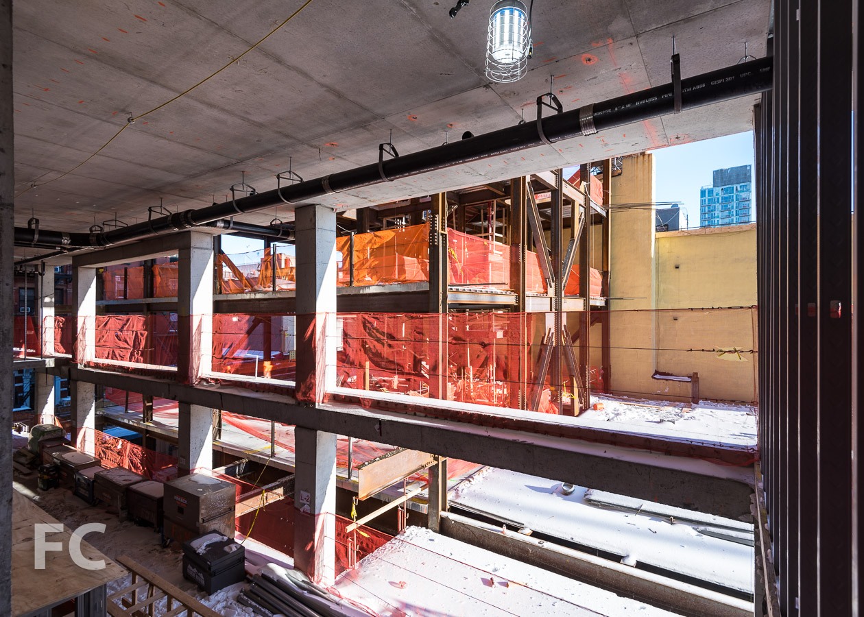 View of the steel structure of the community facility space from the residential tower's concrete structure.