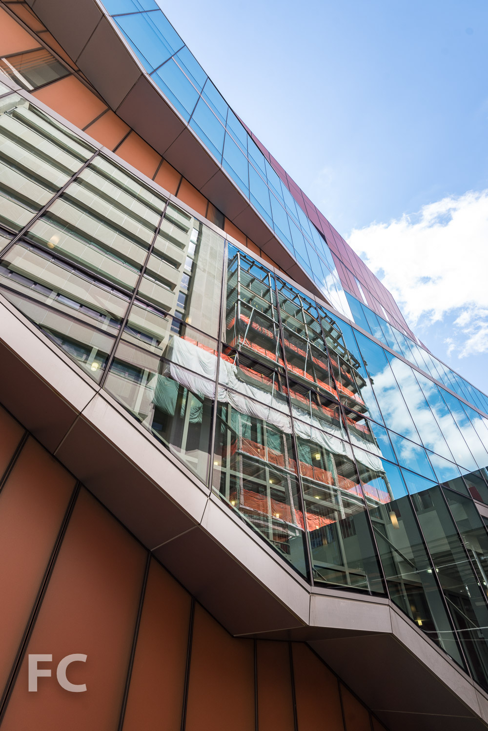 The Milstein Center reflected in the fritted glass façade of The Diana Center.