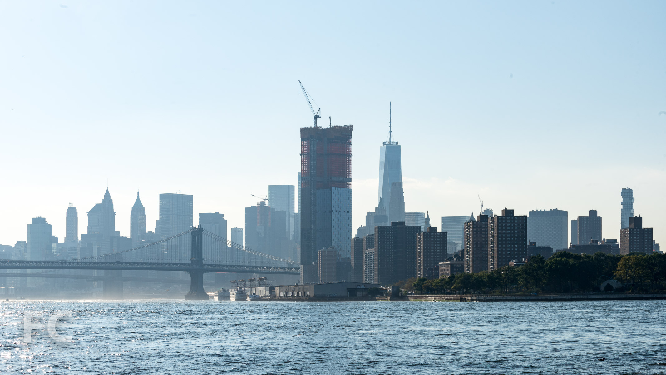 View south from the East River, with One Manhattan Square (center) and One World Trade Center (right).