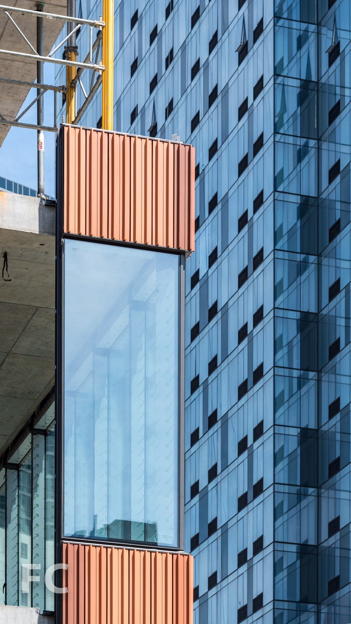 Close-up of the terracotta and glass curtain wall panels.