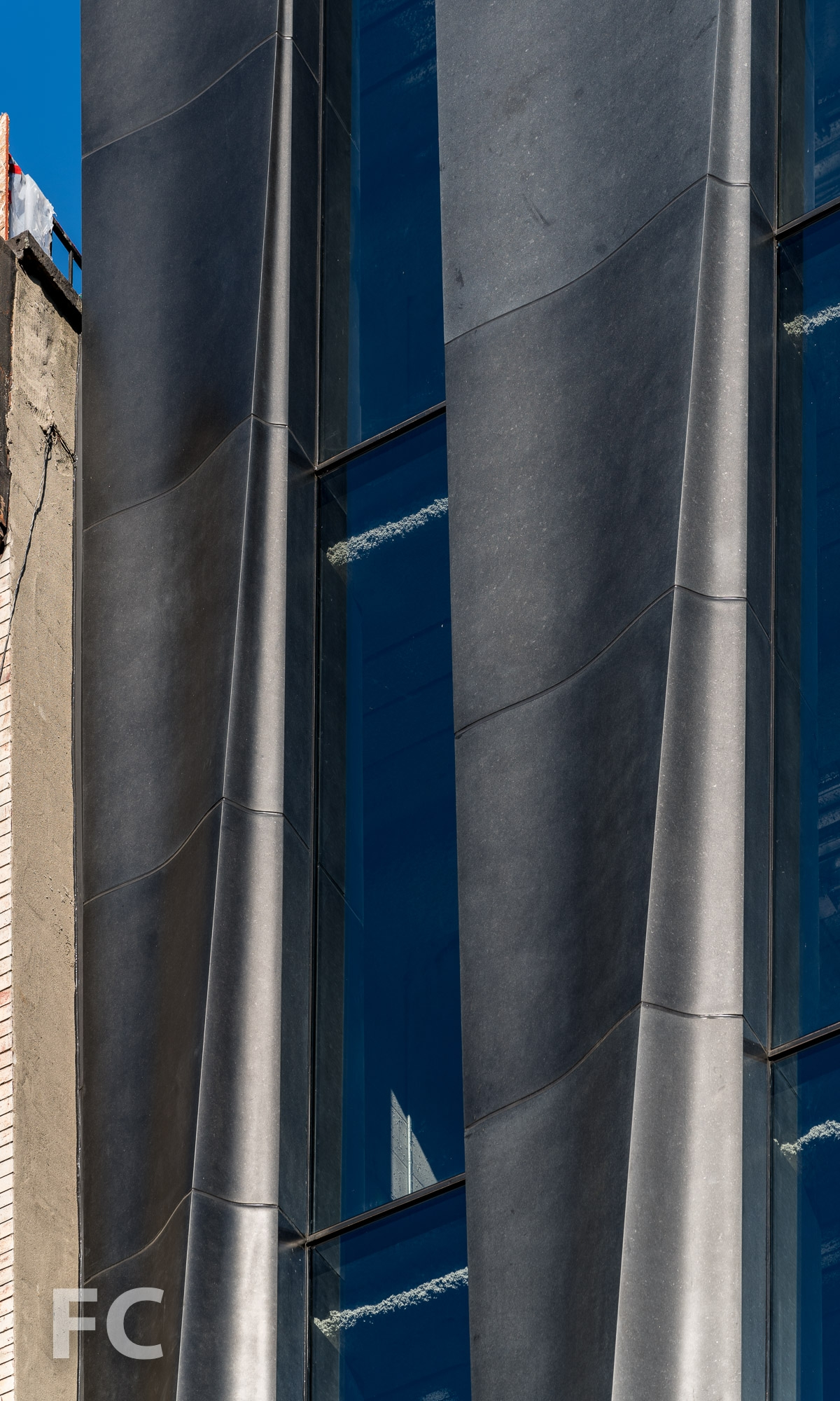 Close-up of the CNC milled stone and glass facade on Mott Street.