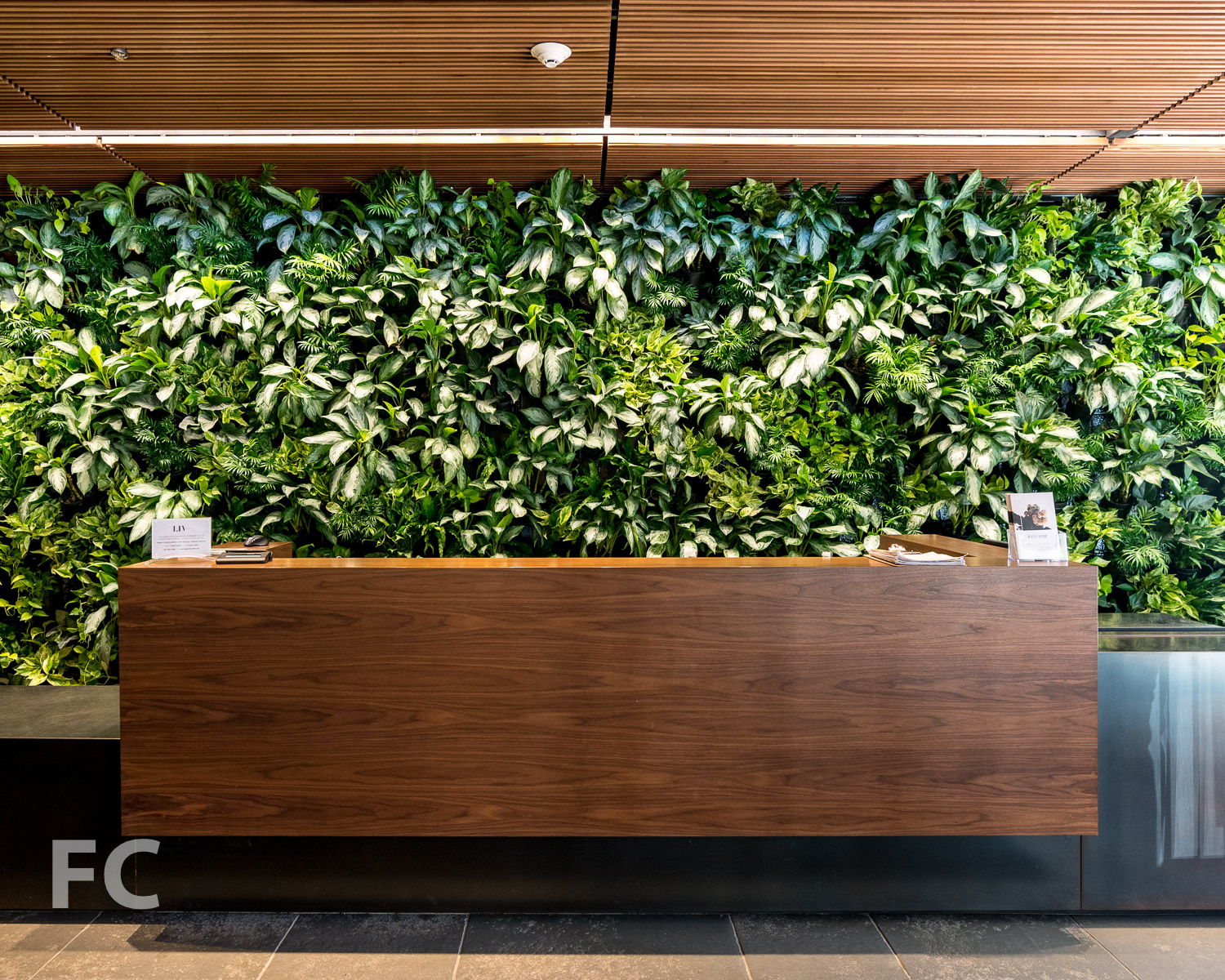 Concierge desk with green wall .