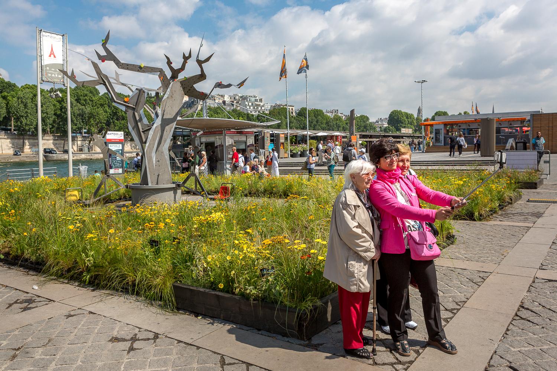 Touristes entrain de se photographier devant une création de l'évènement Petites Fleurs folies. © Sébastien Borda