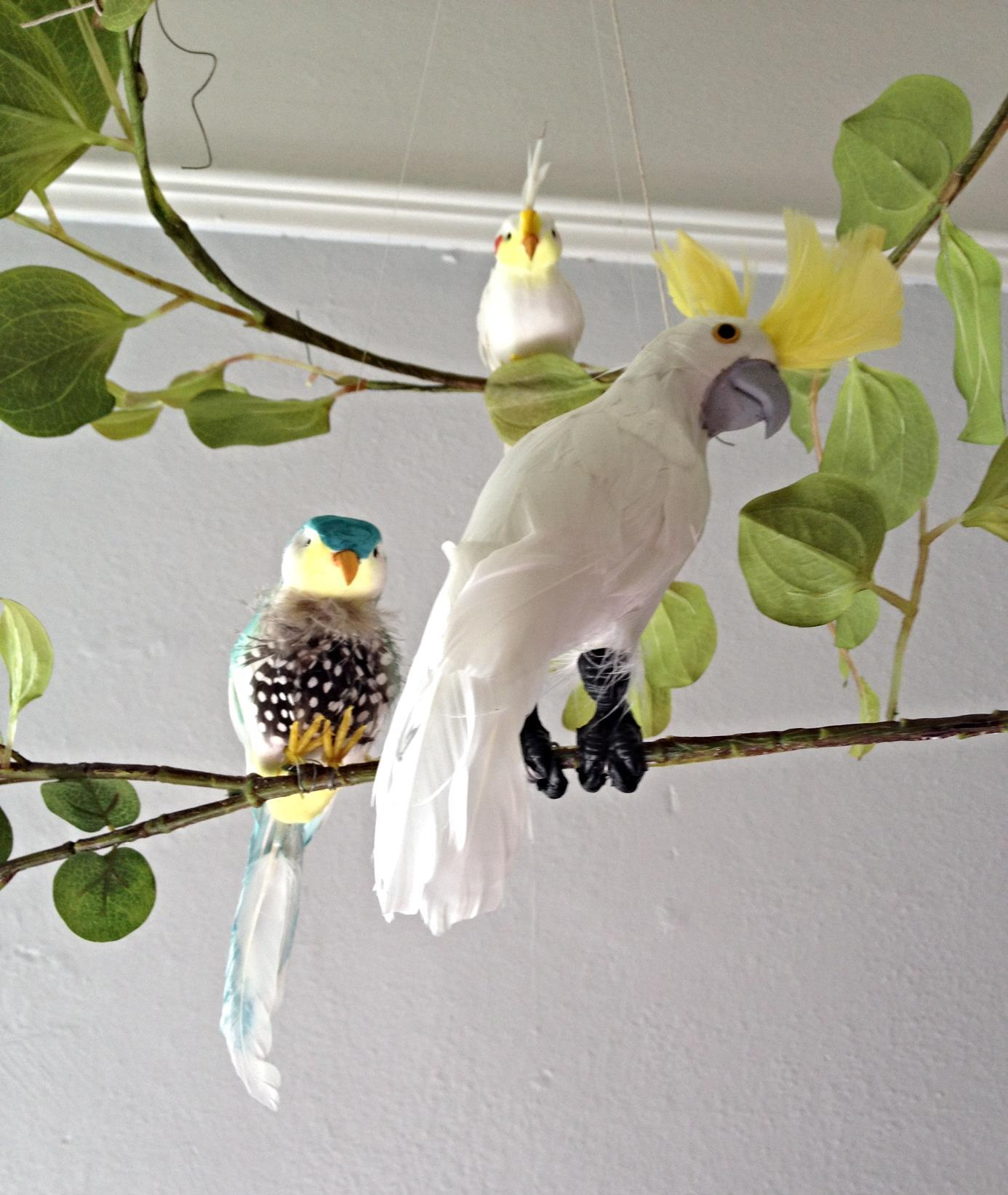 Artificial cockatoos and baby cockatiels, exotic birds for a jungle baby mobile.