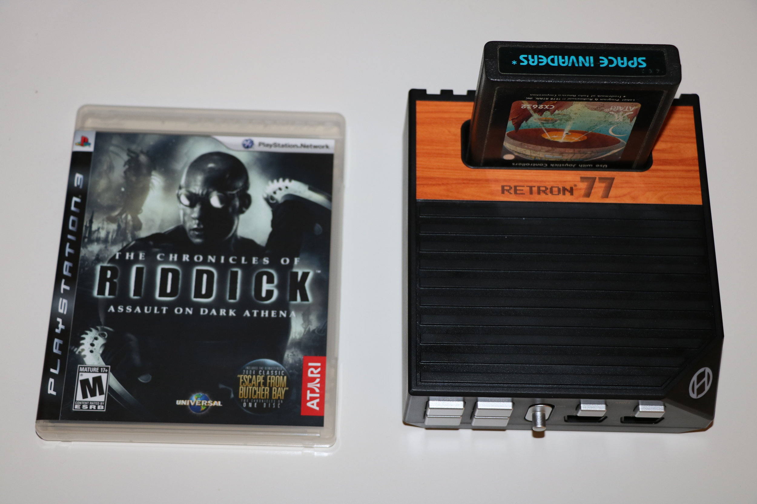The Retron 77 compared in size to one of the most famous releases from Atari (right up there with Warren Robinet's, Adventure).