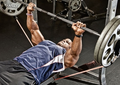 Bodybuilding bench press, abs tucked and muscles actively contracting through entire movement.