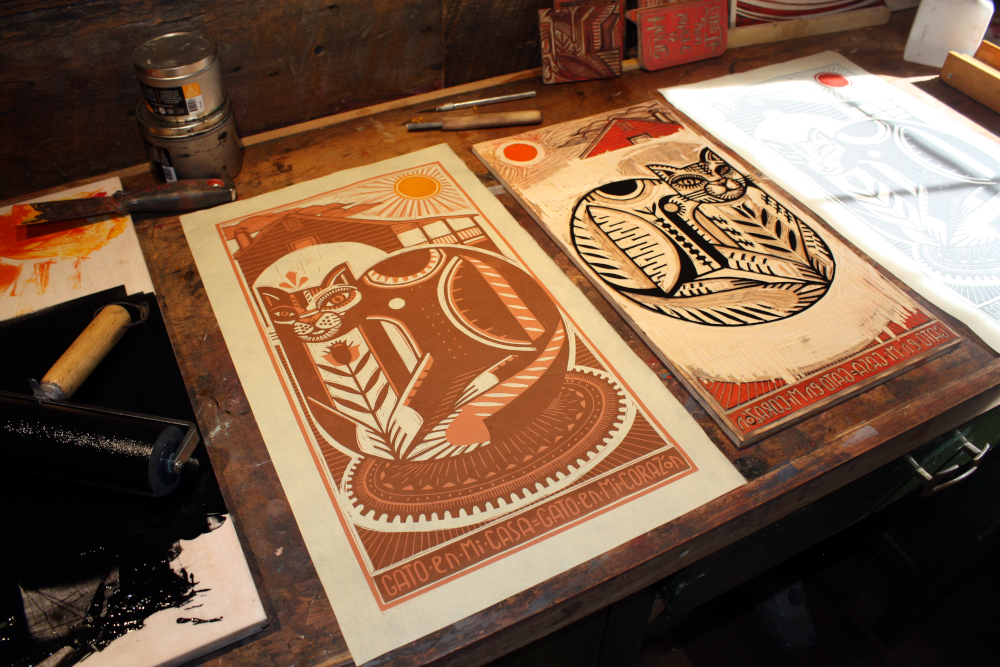 "Here are the prints and block after the SECOND block has been printed and the THIRD and final block has been carved and inked (here you can see my large brayer for inking the black and my small brayer for inking the sun is just out of view.) I was able to ink the sun separately because there was enough space to allow me to ink it without inking other portions of the block.  The challenge of this process is that you must continue to consider after the first block ""whatever I remove stays the color I just printed.""  So after I carved the and printed the first color, I had to hold in my mind that whatever I carved from the block would remain the lightest color (light blue-gray or a light peach.) Then after the next printing I had to hold in my mind that whatever I removed would stay the darker color, and whatever I left on the block would be printed my last color, black.  This requires commitment, anything removed from the block cannot be put back, and after you start the process there is no going back and printing more prints.  As you can see in this picture there is not much left on this block.  It is wonderful actually, I enjoy carving away what I have spent hours carving, it it feels appropriate to the nature of things.  Every act of creation is an act of destruction in its very nature, this is very very clear in this process."