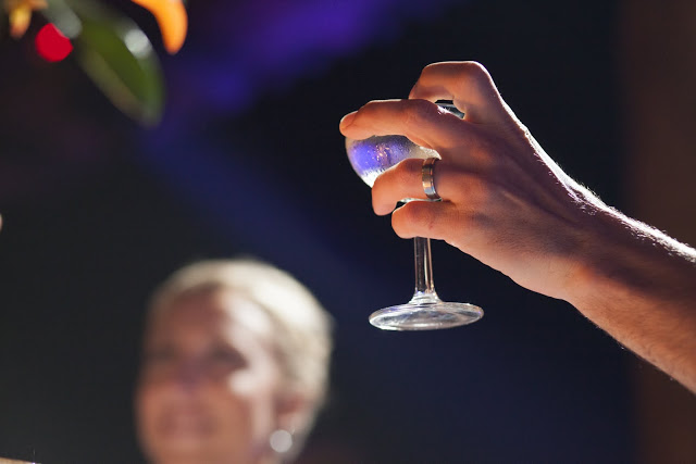 Hand with wedding band holding a glass of champagne