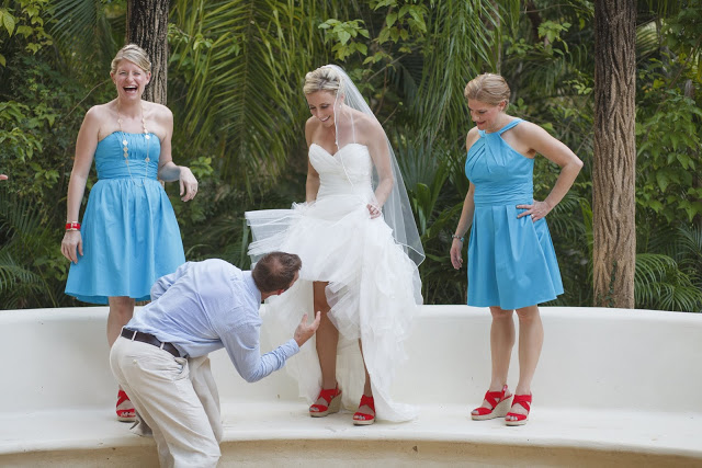 Groom blowing air underneath the bride's dress due to hot weather