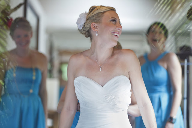 Bride getting her wedding dress laced up before the ceremony, bridesmaids laughing in the background