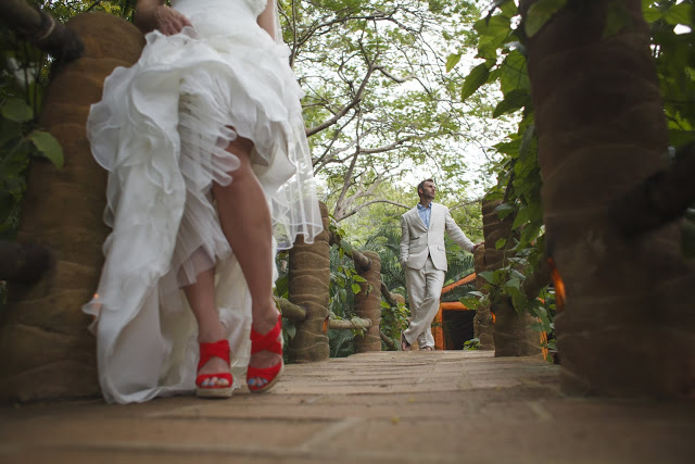 Groom leaning against the rail, the bride's red shoes are shown in the foreground