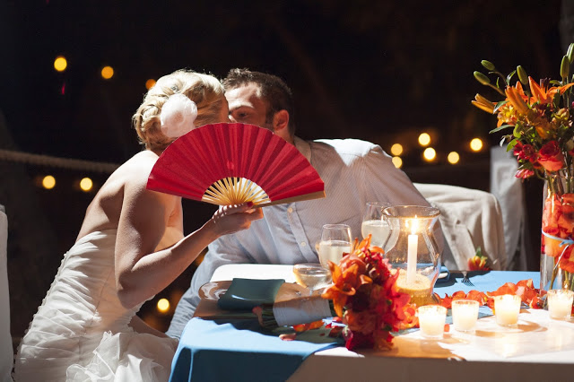 Wedding couple kissing behind a red fan