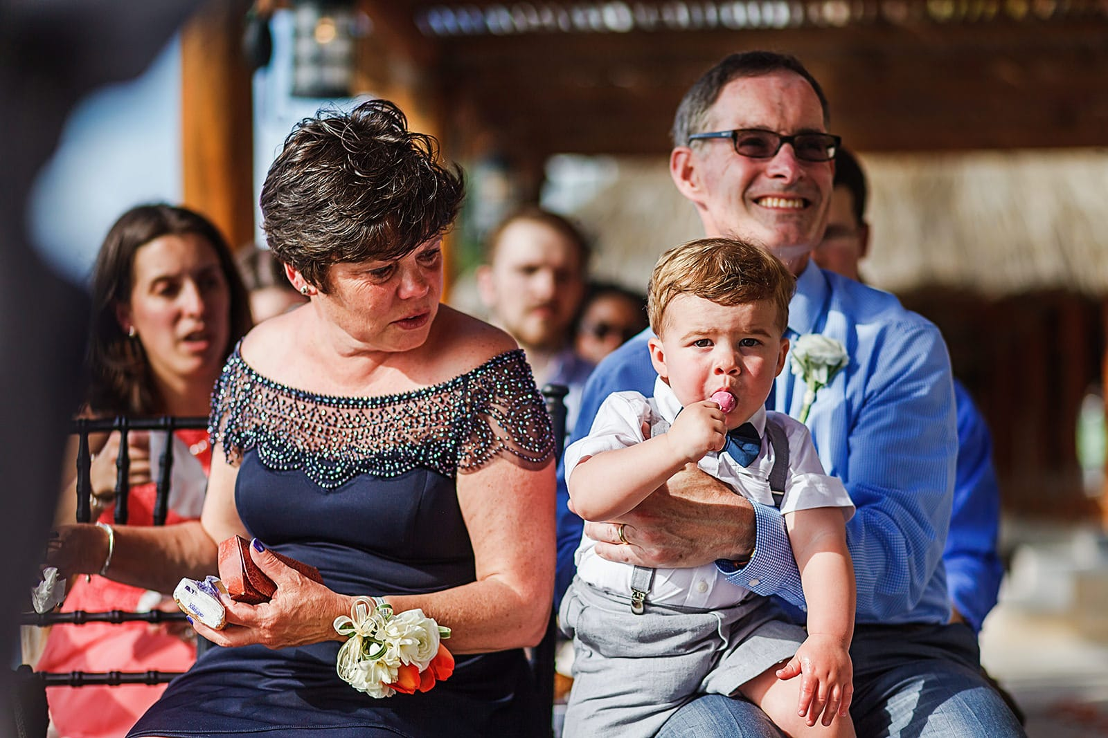Toddler enjoys a lollipop on father-of-the-groom's lap during wedding ceremony