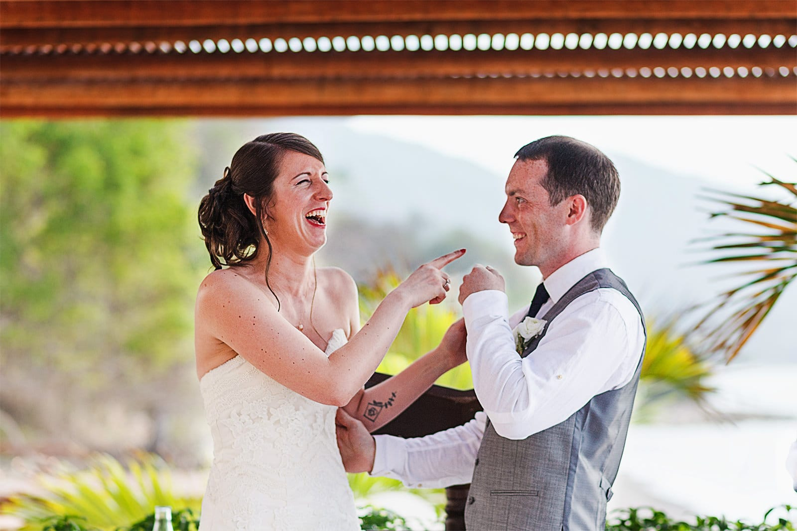 Bride laughs at groom after their first kiss for leaving lipstick on his mouth