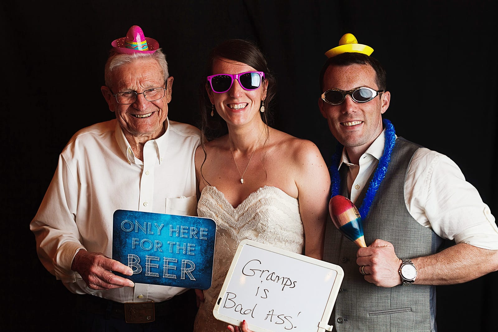 "Bride, groom and gramps wear tiny sombreros and hold signs on the photo booth, the bride's one reads ""Gramps is Bad Ass"""