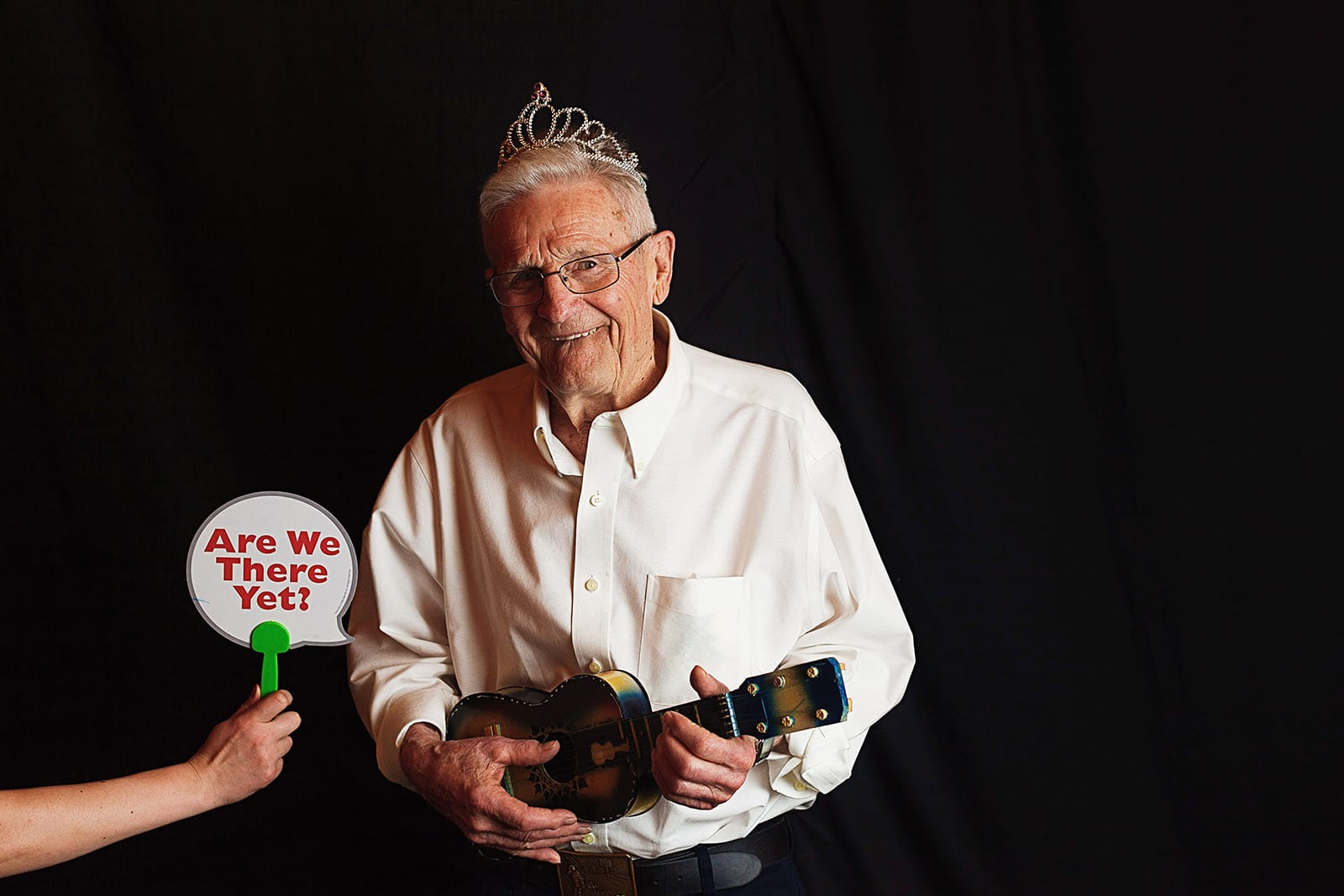 Bride's grandfather wears a tiara and hold a tiny guitar for the wedding photo booth