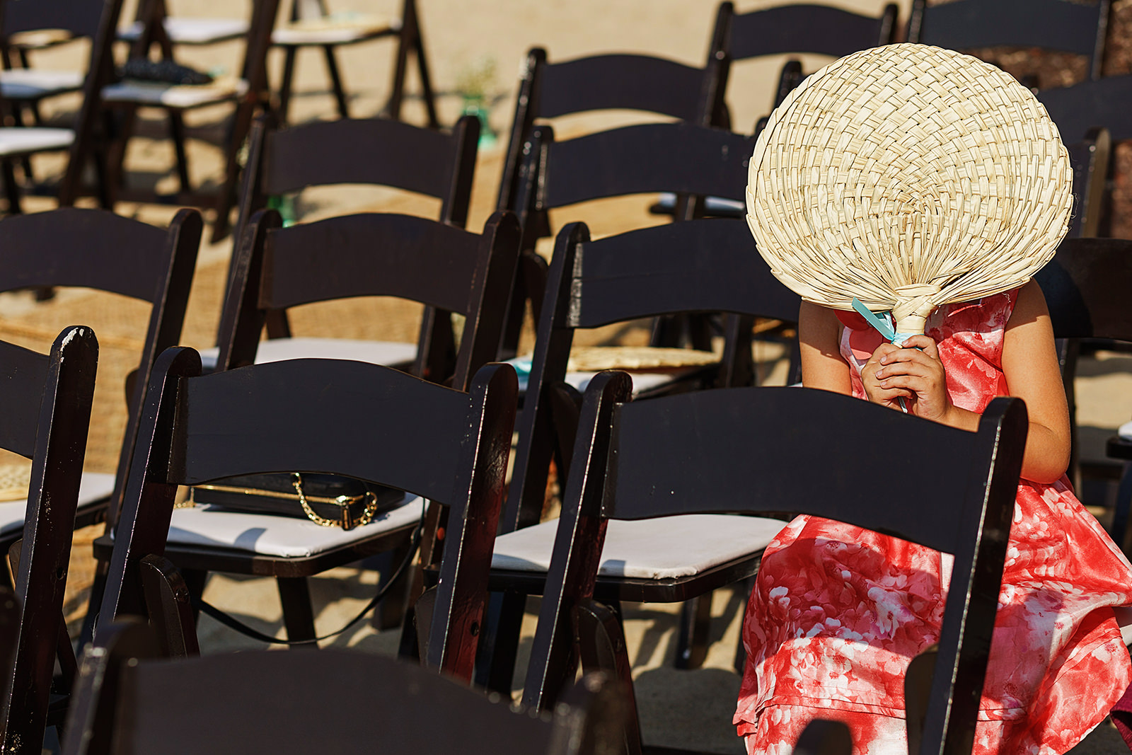 A little girl holds a fan to block the sun from her face and hide from the camera before the ceremony on the beach begins