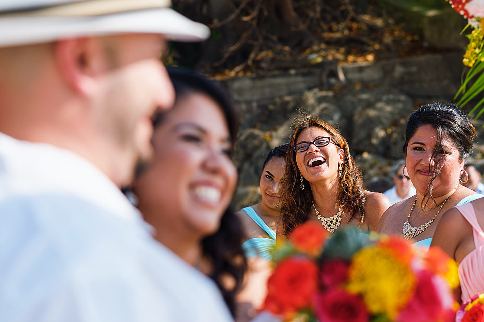 Bridesmaid laughs during beach wedding ceremony, bride and groom can be seen in foreground