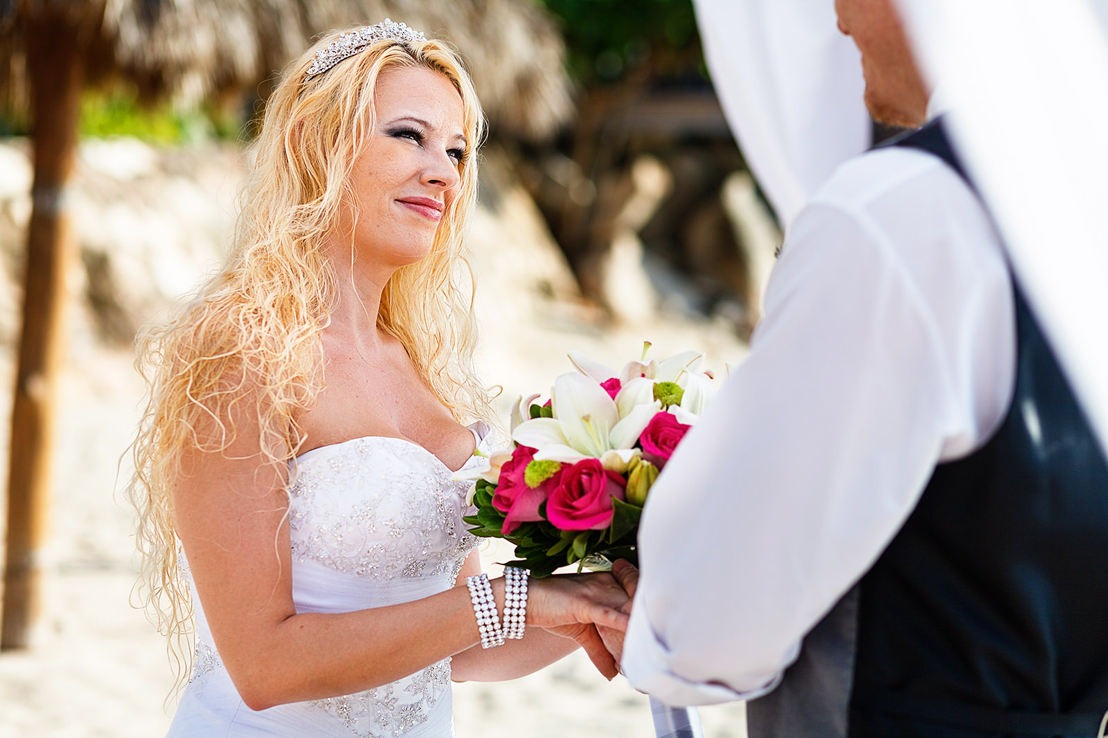 Bride with tiara looking at groom during ceremony on the beach