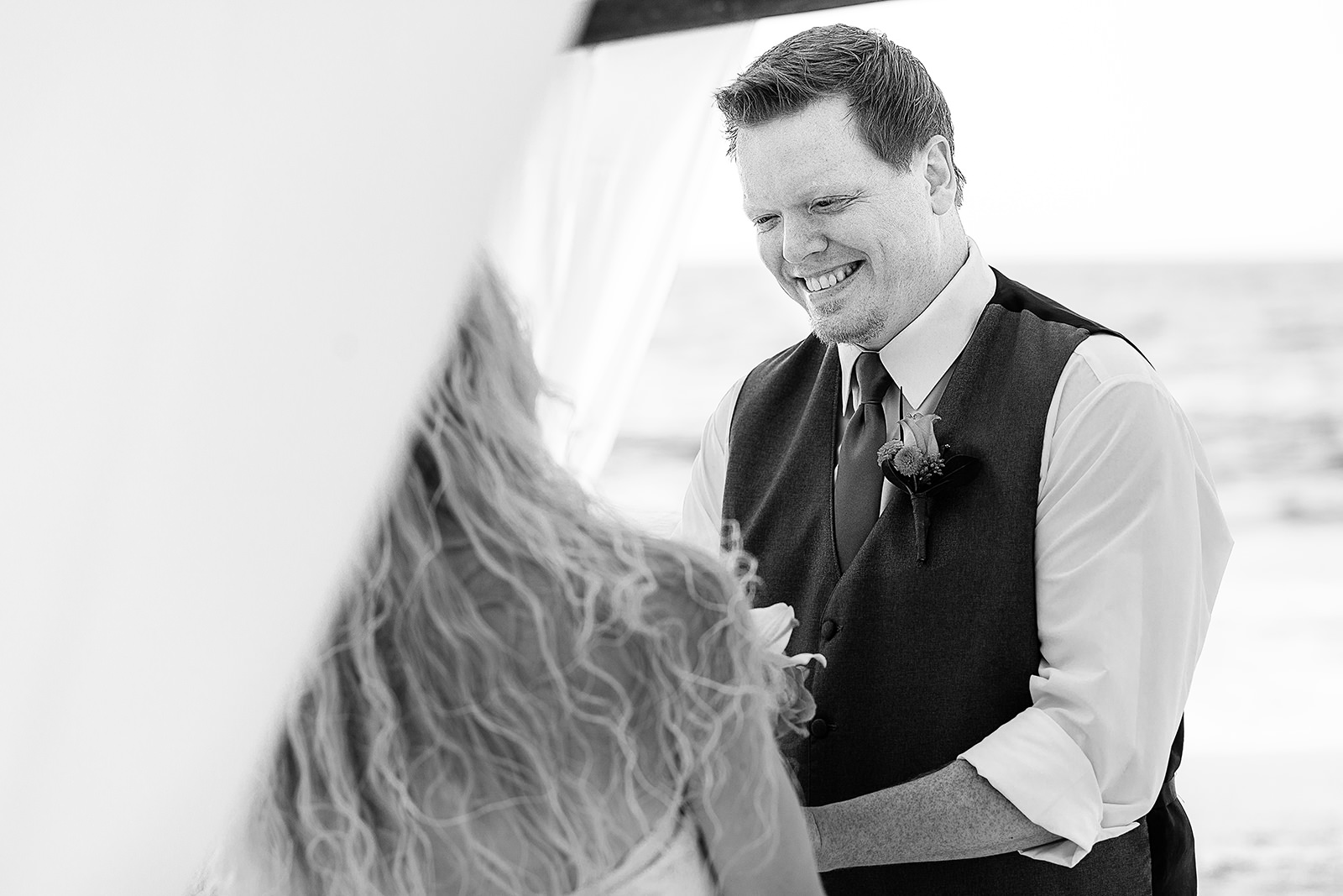 Groom smiling at bride during ceremony on the beach