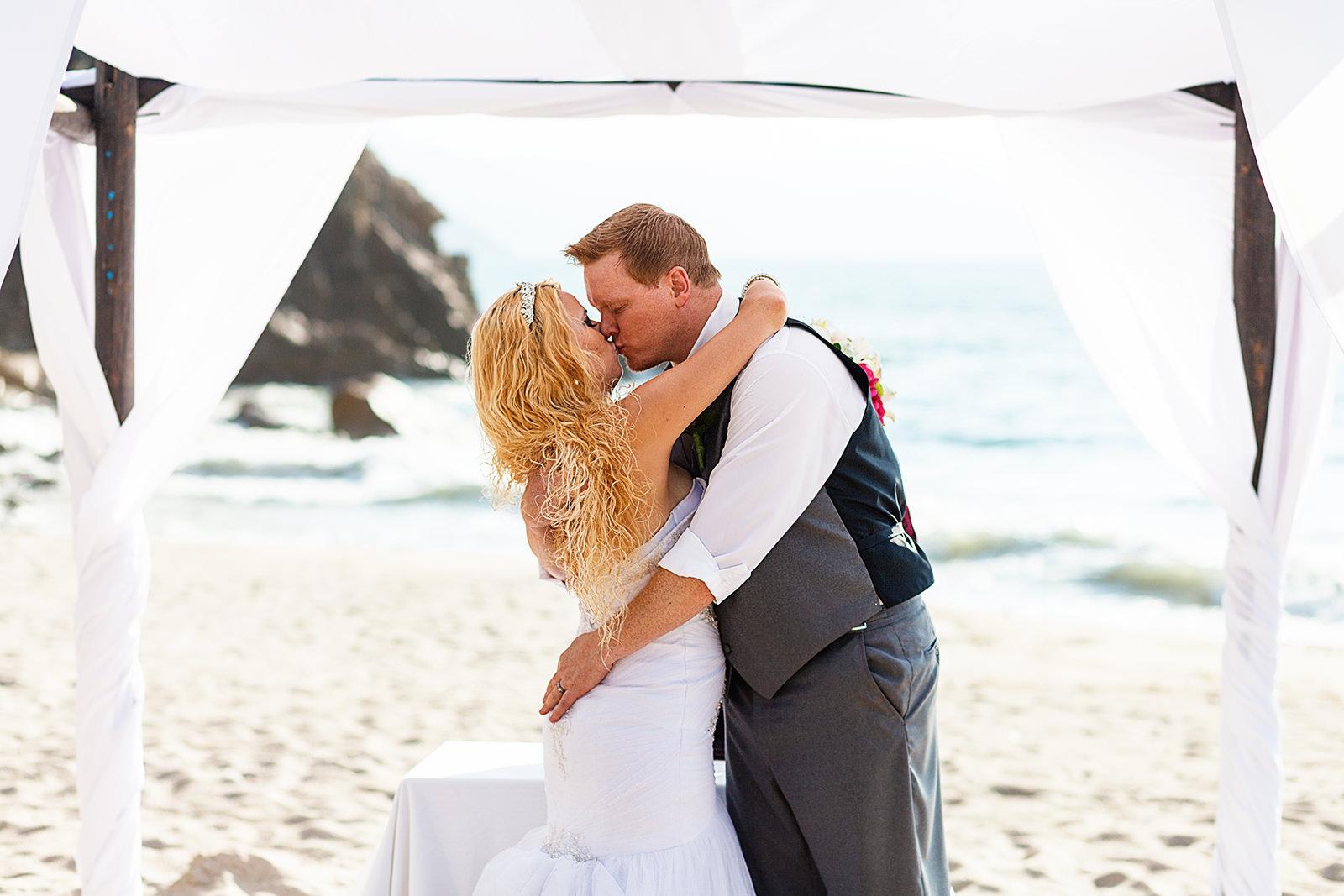 wedding couple's first kiss on their beach ceremony under a chuppahp