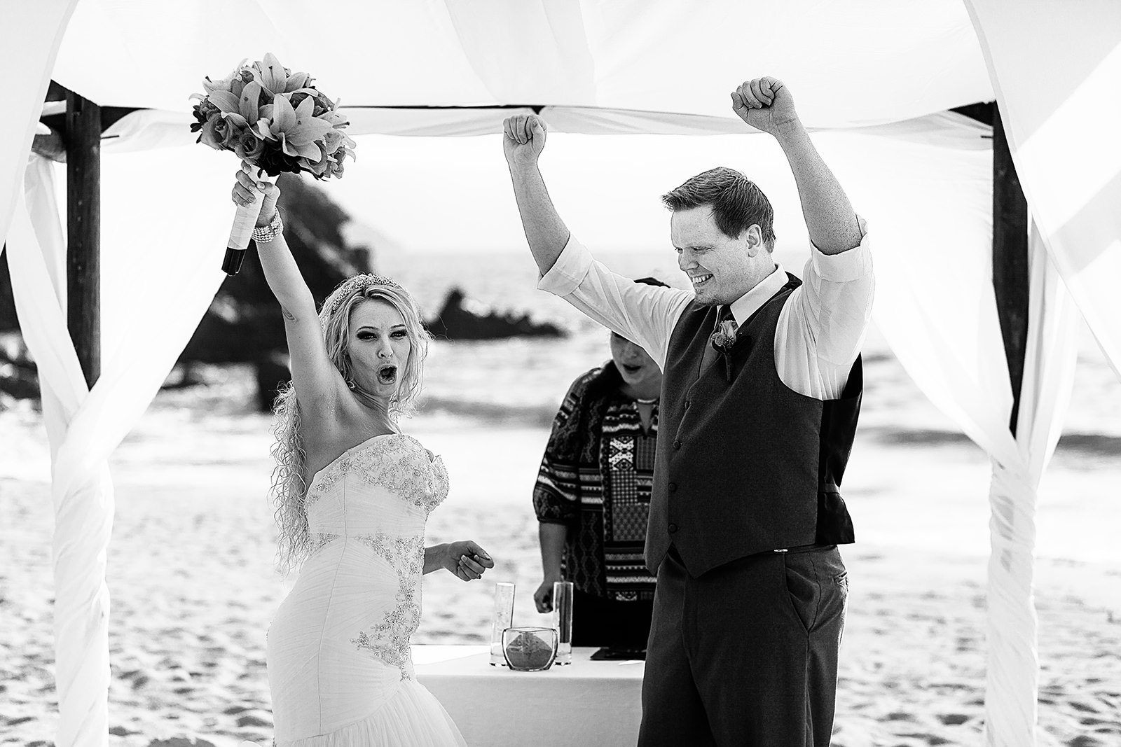 Wedding couple celebrates at ceremony on beach, black and white moment
