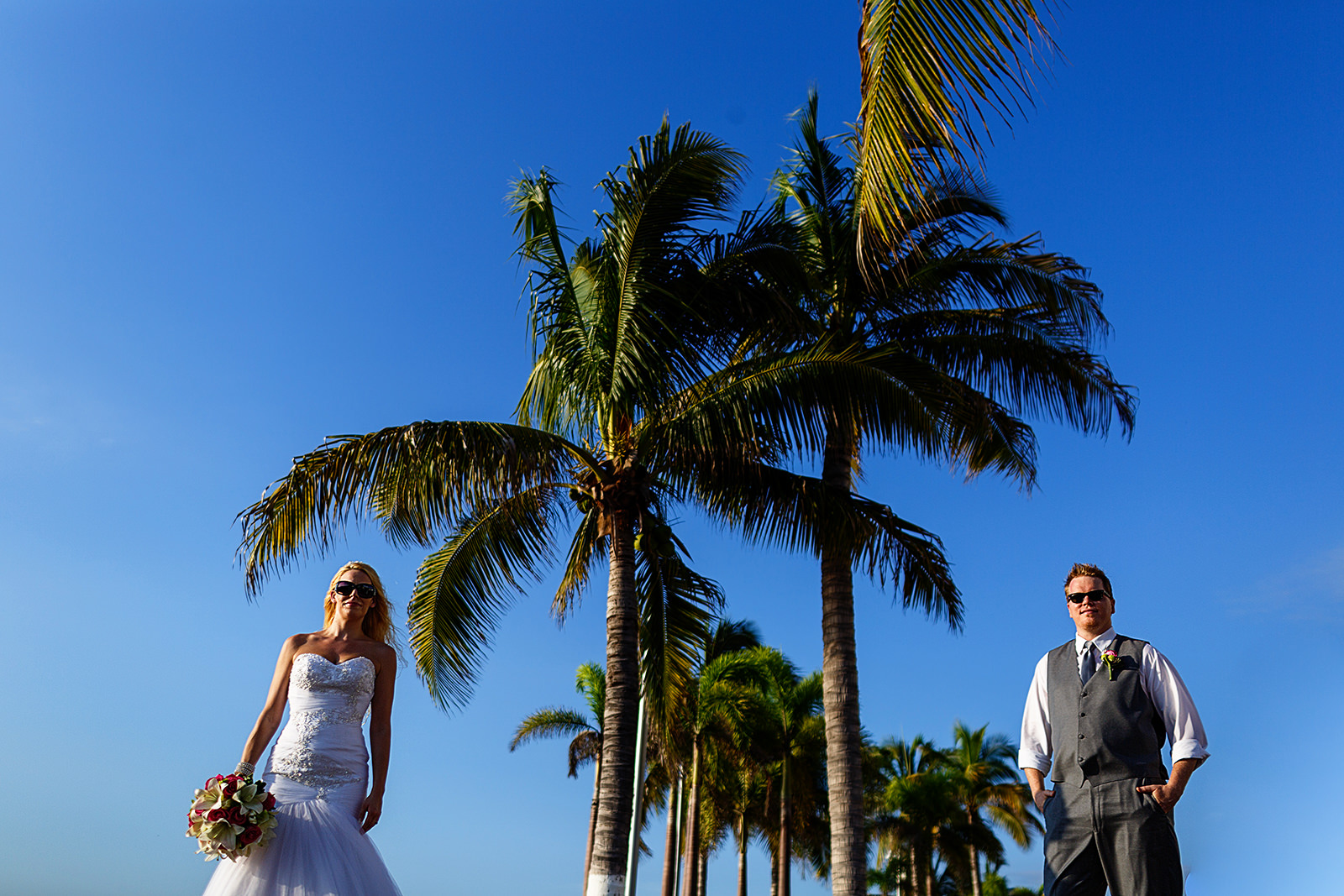 bride and groom portrait with palm trees between them and blue sky as background