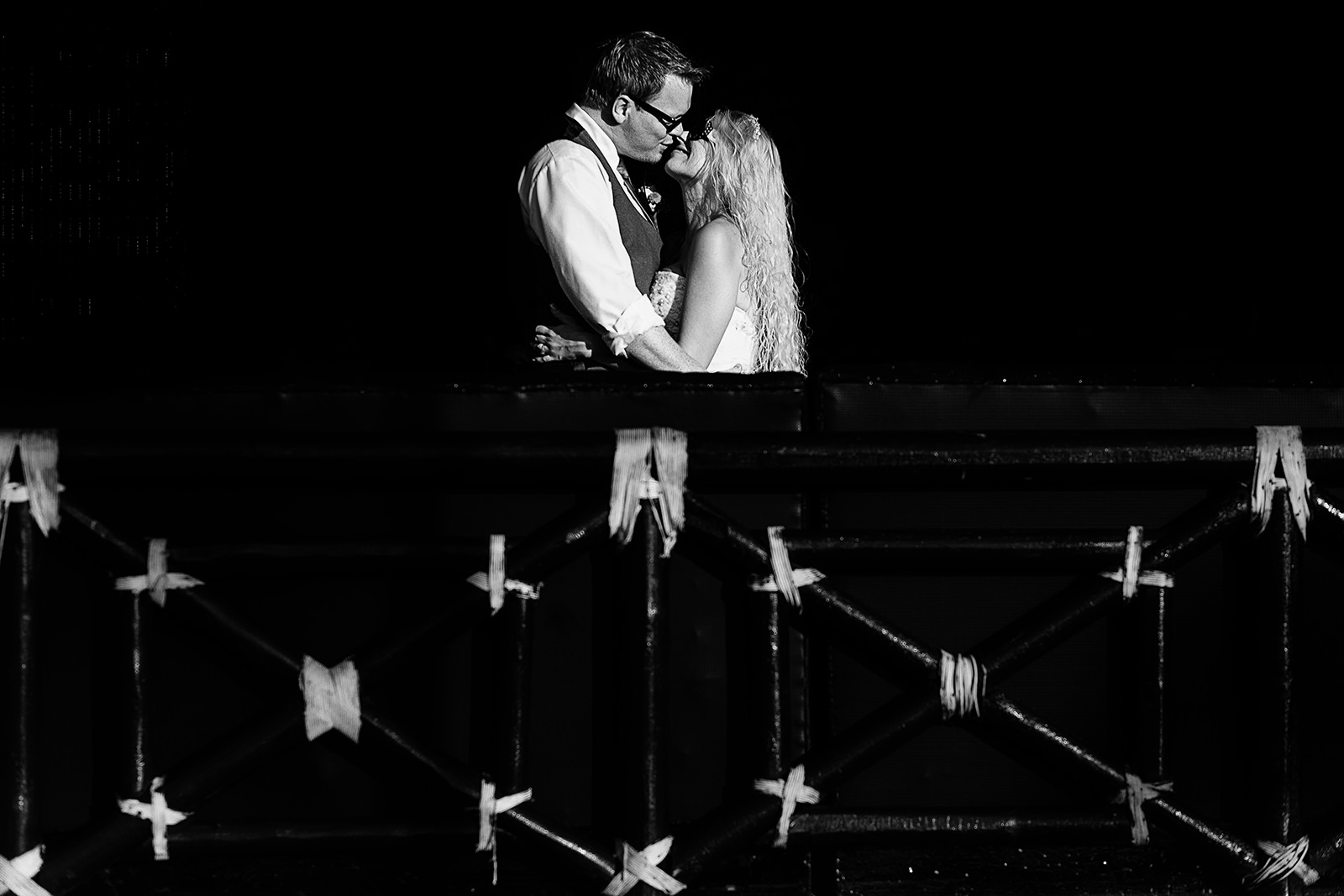black and white kiss of wedding couple against black background