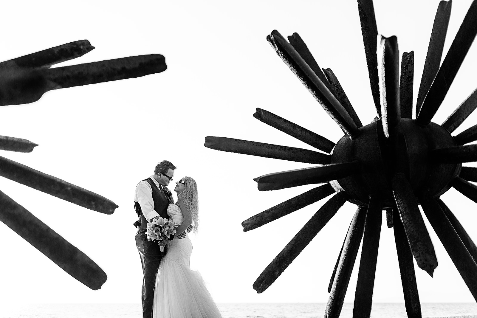 Couple on wedding outfits looking at each other between metal spiky structures
