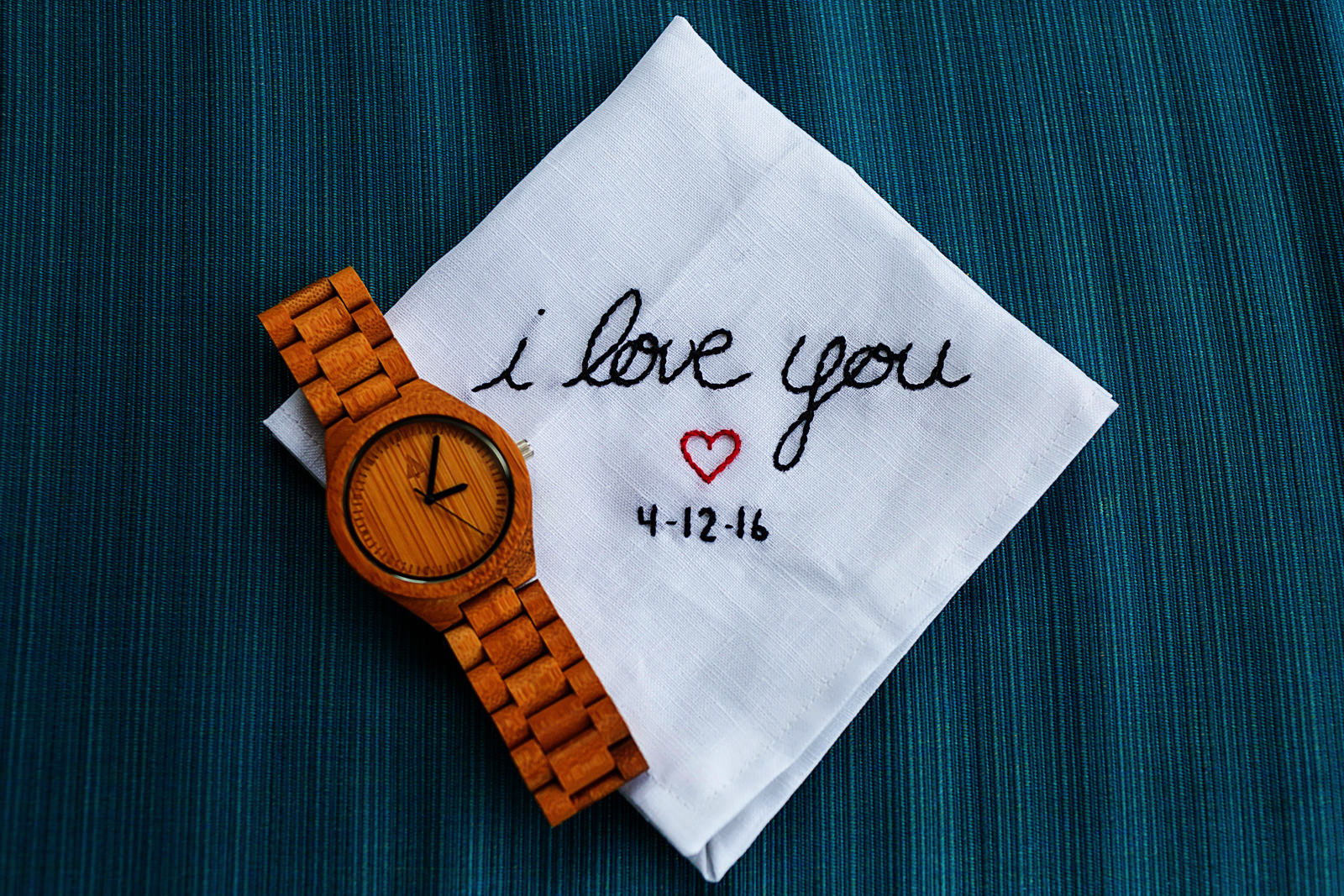 handkerchief with words I LOVE YOU and wedding date embroiled next to wood wrist watch