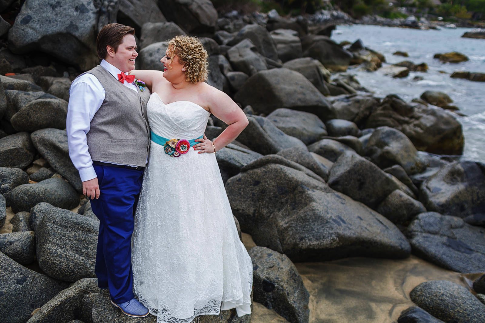 LGBTQ Brides standing on rock by the ocean