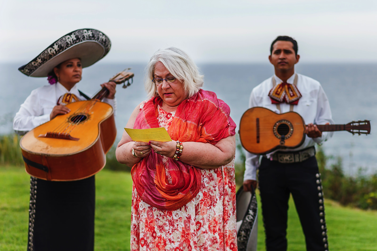 wedding guest reading a few words for ceremony between two mariachi players in background