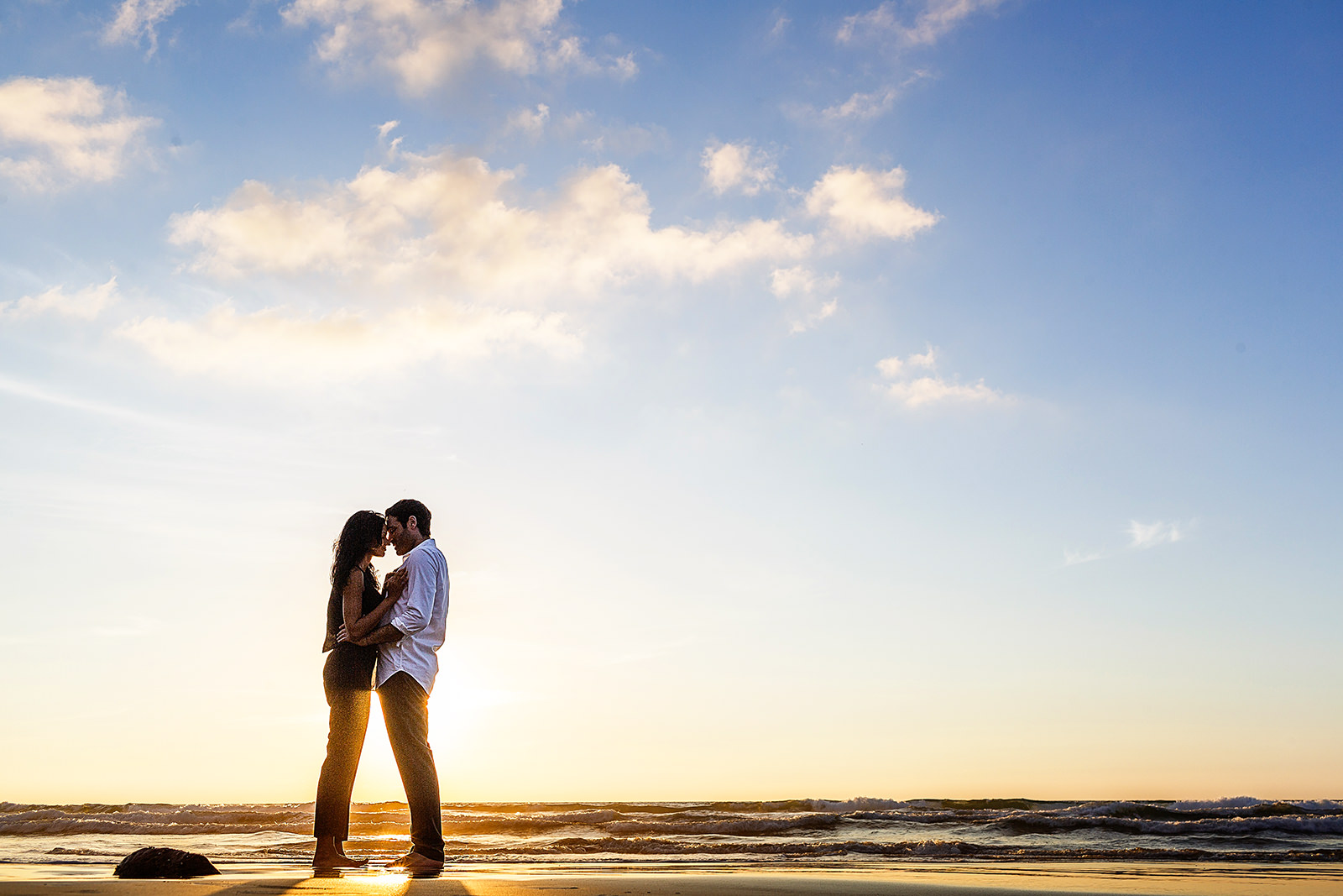 Couple standing and leaning their faces into each other during sunset
