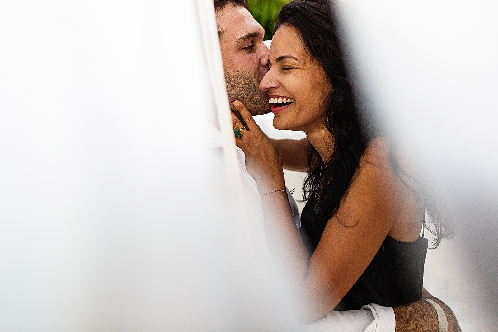 Couple laughing through white blankets