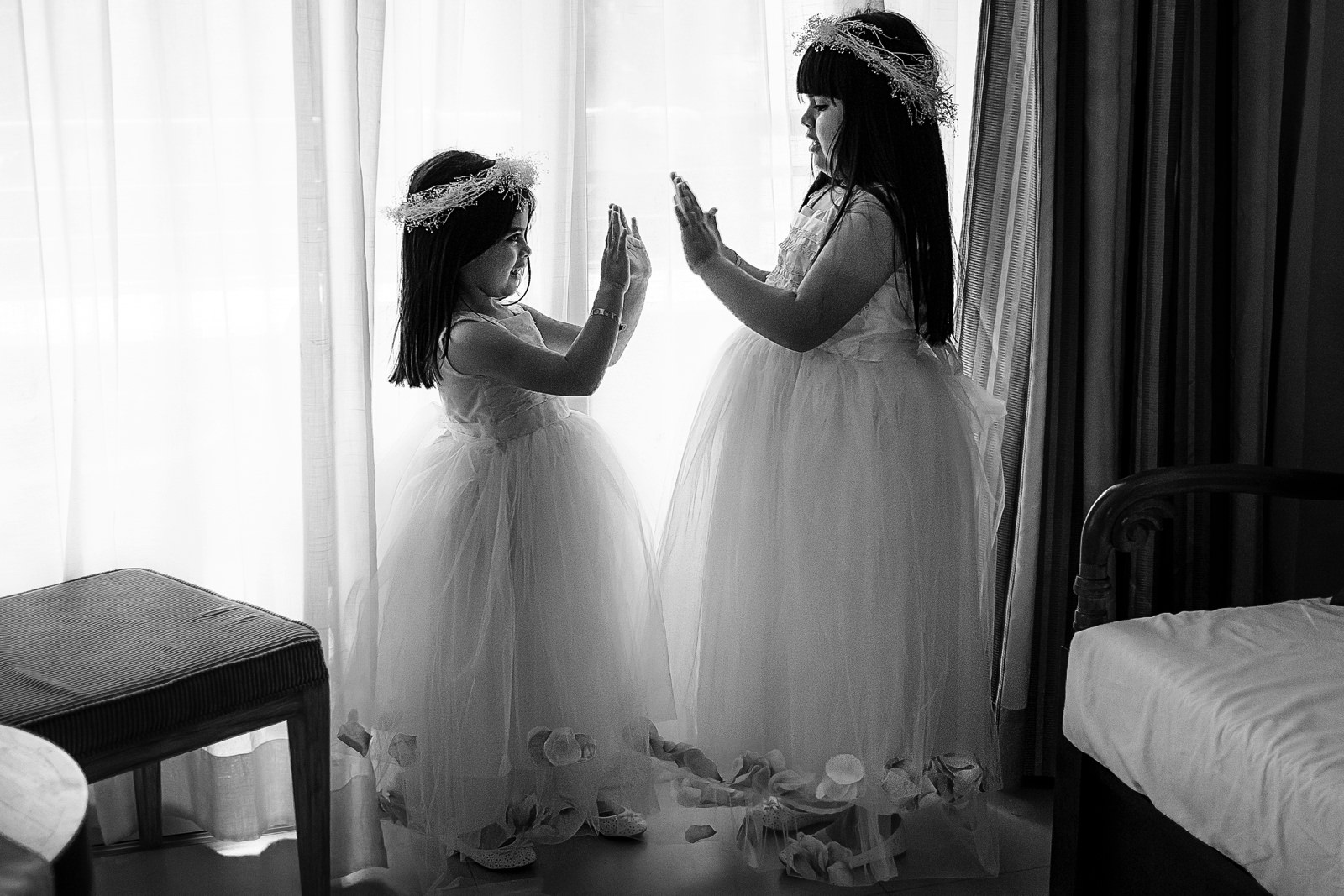 Flower girls playing with their hands on the room before the wedding ceremony