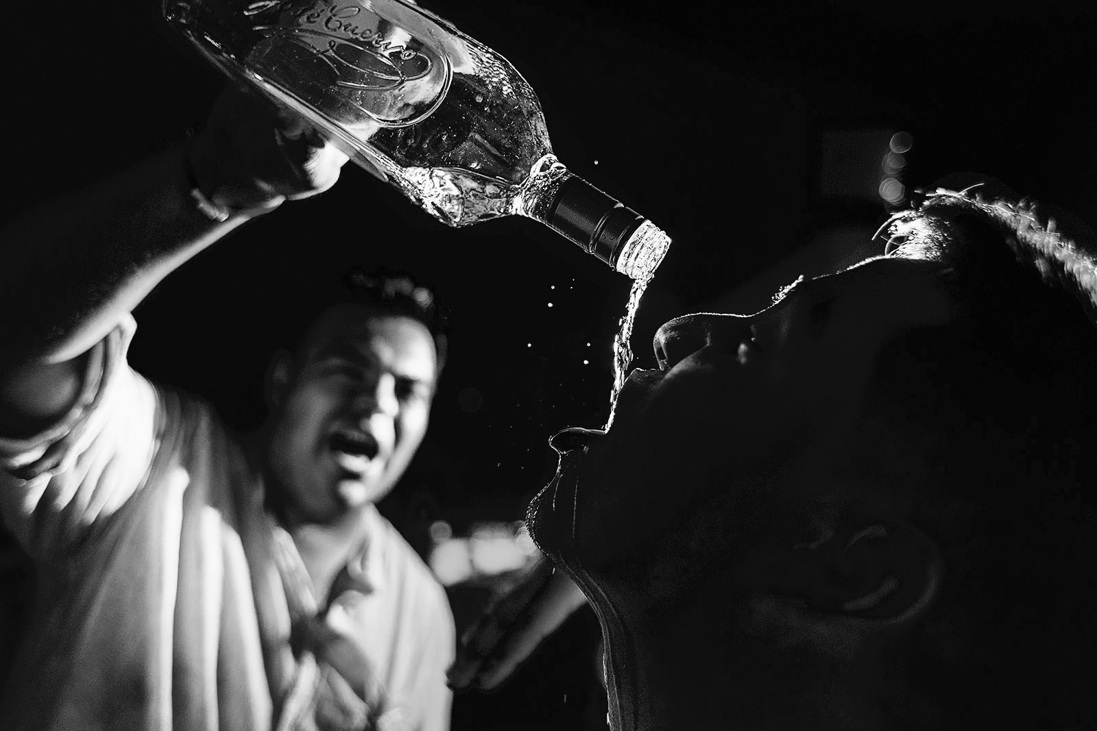 Groom pouring tequila straight from the bottle into a guest's mouth