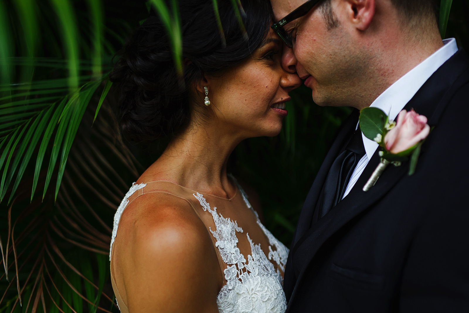 Bride and groom standing close to each other in the middle of palm leaves