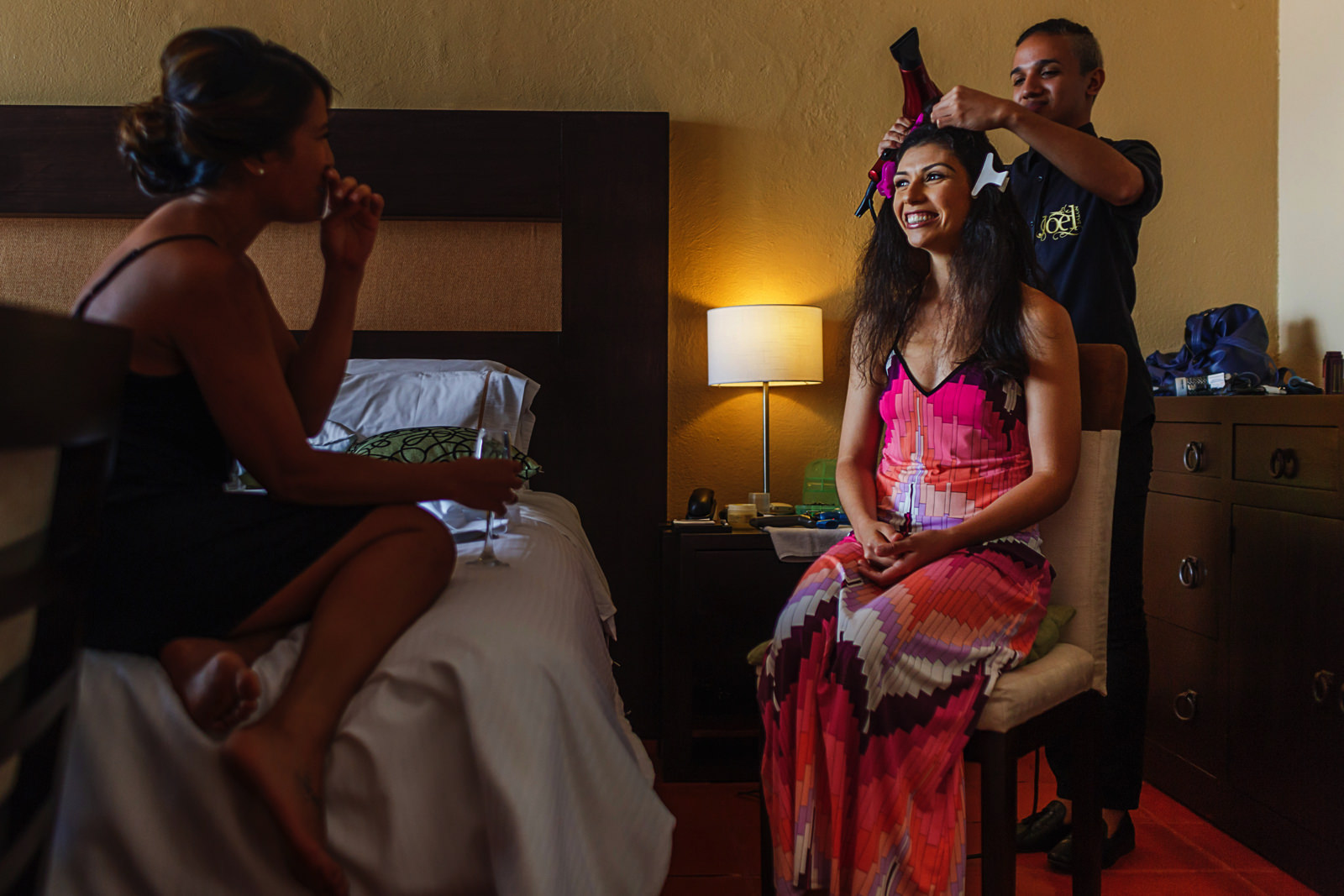 Bride getting her hair done before wedding ceremony while she laughs with bridesmaid