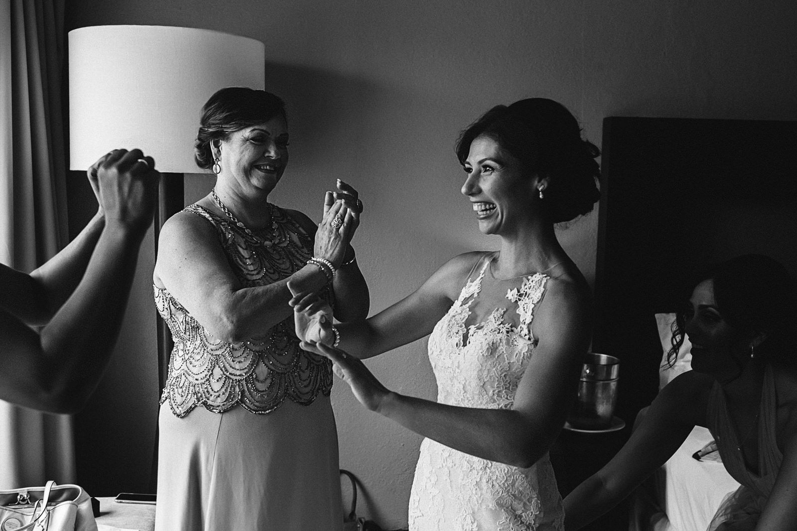 Bride and mother-of-the-bride laughing while bridesmaid help her with the wedding dress