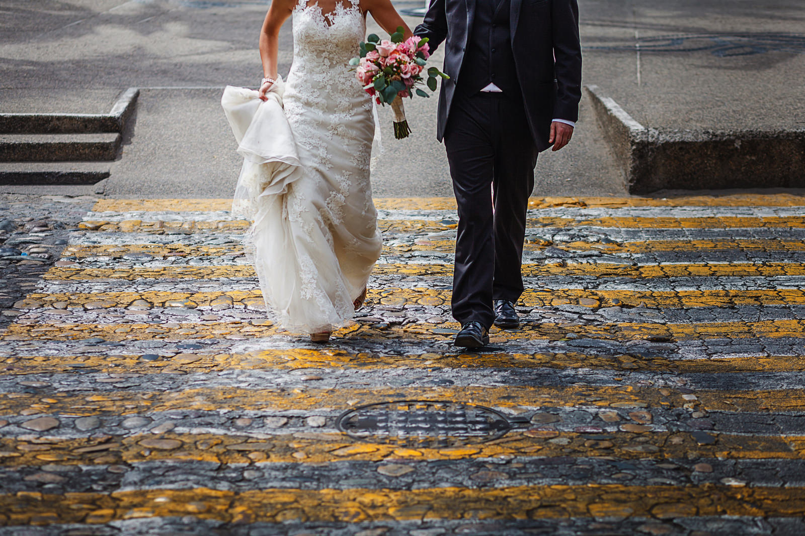 Groom and bride walking on yellow stripes downtown Puerto Vallarta, Mexico
