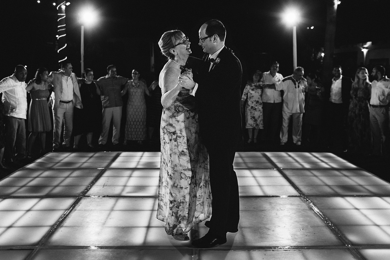 Mother and son dance on retro-iluminated dance floor - black and white photo